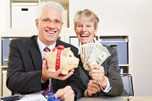 Two elderly happy business people with fan of dollar bills and piggy bank