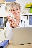 Smiling elderly doctor recommending pills at desk in office