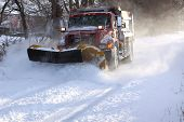 image of cold-weather  - A snowplow truck removing snow from a tree lined rural road on a cold winter day - JPG