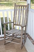 image of screen-porch  - Worn wooden rocking chair on a screened in porch - JPG