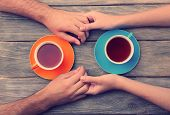 stock photo of sweetheart  - Tea cups and holding hands at the wooden table - JPG
