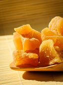 pic of home remedy  - Closeup candied crystallized ginger candy pieces on wooden spoon - JPG