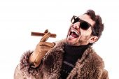 foto of hustler  - a young and rich man wearing a sheepskin coat isolated over a white background holding a cigar - JPG