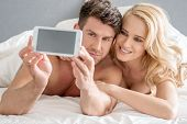 foto of two women taking cell phone  - Middle Age Romantic Lovers Taking Sweet Photos on Bed with White Cover - JPG