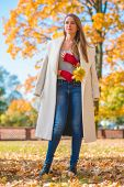 picture of overcoats  - Stylish woman in autumn fashion wearing an elegant white overcoat and red mittens standing outdoors in a park with a handful of yellow fall leaves - JPG