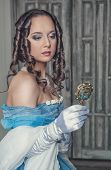 image of pompous  - Young beautiful medieval woman in long blue dress with mirror in the old room - JPG