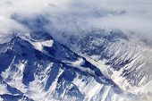foto of snow capped mountains  - Top view on snow mountains and glacier in mist - JPG