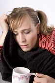 image of feeling better  - A woman who is sick holding her blanket and tissue looking into a cup with something warm in it to help her feel better - JPG