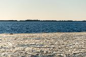 picture of shipyard  - frozen beach near shipyard and sea port with rays of sun and wavebreaker - JPG