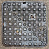 stock photo of manhole  - square metal manhole cover with a raised pattern on the street - JPG