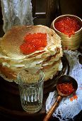 foto of tumbler  - Pancakes with red caviar and vodka in a thick glass tumbler - JPG