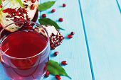 picture of pomegranate  - fresh pomegranate juice and ripe pomegranate seeds on a blue wooden background - JPG