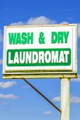 stock photo of laundromat  - An old green and white laundromat sign against a blue background - JPG