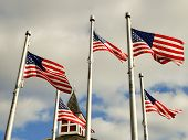 stock photo of flag pole  - red white and blue flags on a pole with american architecture - JPG