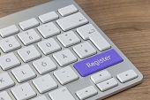 stock photo of keyboard  - Register written on a large blue button of a modern keyboard on a wooden desktop - JPG