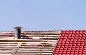 picture of roof tile  - New metallic tiled roof with smokestack under constrution - JPG