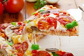 pic of hot fresh pizza  - A slice of hot pizza deluxe with pepperoni mushrooms peppers  - JPG