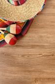 pic of maracas  - Mexican background with sombrero straw hat maracas and traditional serape blanket or rug on a wood floor - JPG
