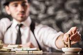 picture of gangster  - Confident gangster man is smoking a cuban cigar - JPG