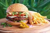 foto of hamburger-steak  - Tasty hamburger and french fries on green grass - JPG