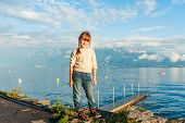 stock photo of pullovers  - Outdoor portrait of a cute little girl wearing beige pullover and jeans - JPG