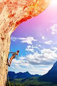pic of climbing wall  - female rock climber climbs on a rocky wall against a blue cloudy sky - JPG