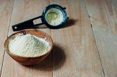 picture of chickpea  - Chickpea flour in old wooden bowl on wooden background - JPG