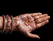 picture of finger-painting  - Wedding rings in Woman palm with henna painting on black background - JPG