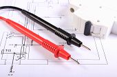picture of electrical engineering  - Cables of multimeter and electric fuse lying on construction drawings of house electrical drawings and tools for engineer jobs - JPG