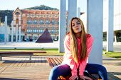 picture of charming  - Portrait of attractive school girl posing for camera while giving a kiss charming caucasian student sitting on the wooden campus bench against university building cheerful teenager - JPG