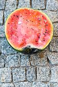 stock photo of rotten  - Rotten watermelon on a grey stone background - JPG