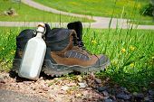 picture of canteen  - Hiking boots with a canteen stand on the wayside in front of a summer meadow - JPG