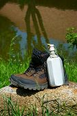 image of canteen  - Hiking boots and a canteen on a rock in front of a pond - JPG