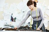 stock photo of tailoring  - young female tailor designer working with cloth fabric in workshop - JPG
