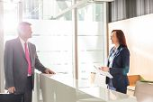 stock photo of receptionist  - Businessman talking with receptionist in office - JPG