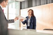 picture of receptionist  - Businessman receiving document from receptionist in office - JPG