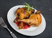 foto of roast duck  - Roast duck legs with cranberries and fresh rosemary on white plate - JPG