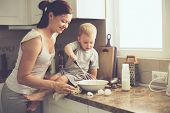 Постер, плакат: Mom with her 2 years old child cooking holiday pie in the kitchen to Mothers day casual lifestyle p