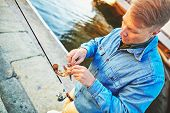 picture of street-rod  - Man preparing to release fish caught on the peir - JPG