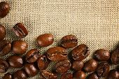 stock photo of sackcloth  - Frame of coffee beans on color sackcloth background - JPG