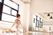 foto of leg-split  - Young Ballering Wearing Pink Tutu Doing Splits in Sunny Dance Studio and Monitoring Posture in Reflection in Mirror - JPG