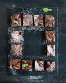 image of brownie  - Dark chocolate and raspberry brownie squares on black stone board over black grunge background - JPG