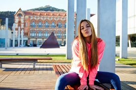 image of sitting a bench  - Portrait of attractive school girl posing for camera while giving a kiss charming caucasian student sitting on the wooden campus bench against university building cheerful teenager - JPG