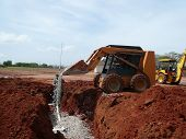 image of septic  - Pouring Rock into an anerobic septic system. Man in the pit is using a level system to make sure the rocks pour level