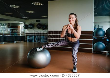 poster of Beautiful Young Woman Stretching With A Pilates Ball In Fitness Gym And Doing Exercises With Fit Bal