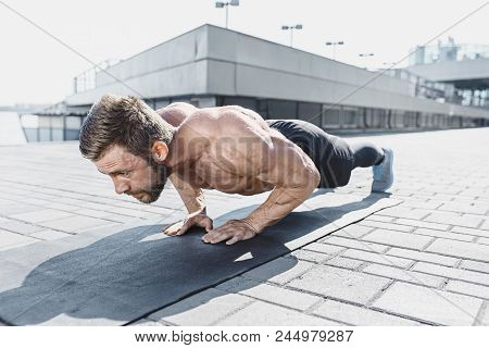 poster of Fit Fitness Man Doing Fitness Exercises Outdoor At City Background. He Doing Hamstring Leg Exercise