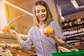 Portrait Of Cheerful Woman Choosing Between Two Oranges At Big Grocery Supermarket. Beautiful Young  poster