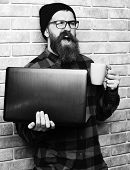 Bearded Man, Long Beard. Brutal Caucasian Happy Unshaven Hipster Holding Laptop With Mag Or Cup In R poster