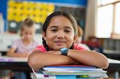 Portrait of cute little schoolgirl leaning on stacked books in classroom. Happy young latin girl in  poster