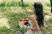 Side View Of Young Woman In Dress Holding Retro Bicycle With Wicker Basket Full Of Ripe Apples At Co poster